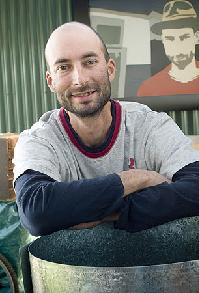 Melbourne artist, Andre Sardone, with his distinctive self portrait in the background